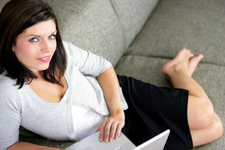 Smart woman lying on a sofa with her laptop photo