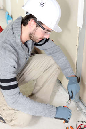 cable cutter: Electrical worker testing socket Stock Photo