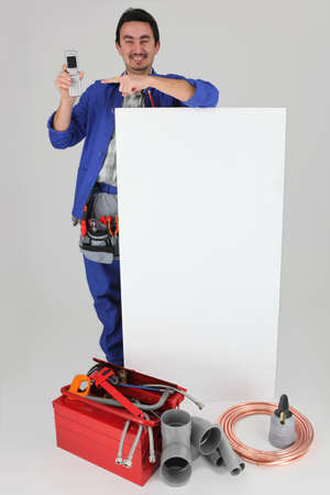 handyman with many tools showing a cell phone Stock Photo - 11971701