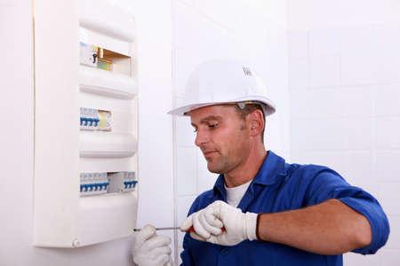 descarga electrica: El hombre reparar un interruptor de circuito Foto de archivo
