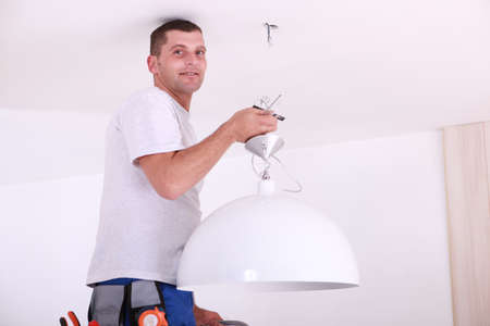 Man installing a ceiling light photo