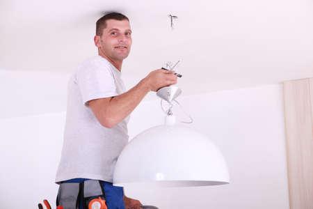 Man installing a ceiling light photo