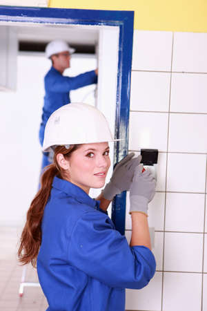 Female electrician fixing wall socket photo