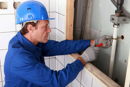 Plumber working on water pipes photo