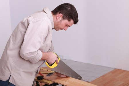sawing: Man sawing laminate flooring