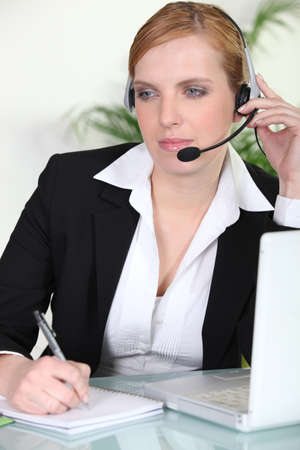 Woman using a headset at her laptop photo