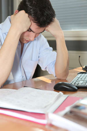 preoccupation: Man depressed at his desk Stock Photo