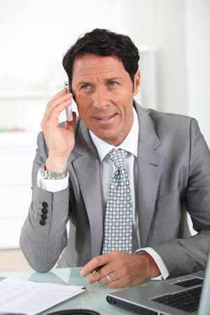 sales assistant: Businessman on the phone smiling Stock Photo