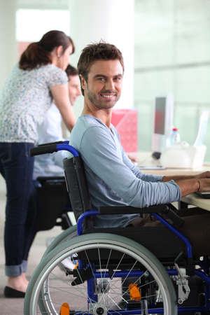 equal: Man in wheelchair at work Stock Photo