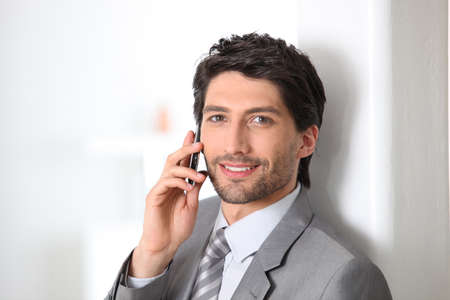 Smiling businessman using a cellphone photo