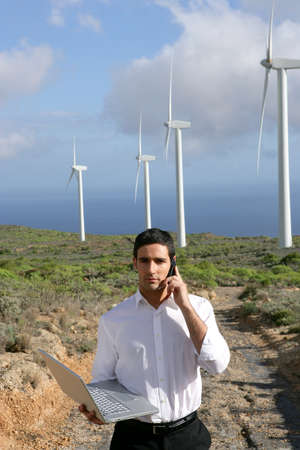 Man with laptop stood by wind farm photo
