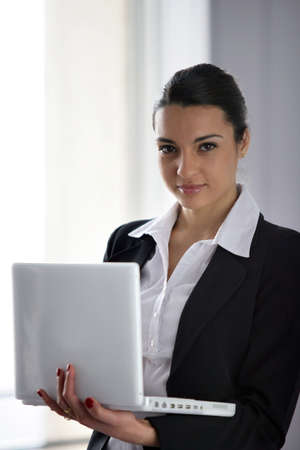 Brunette businesswoman holding laptop photo