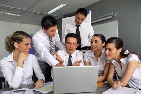 Business team gathered around laptop Stock Photo - 11993649