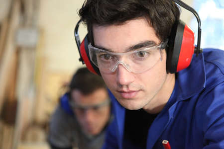 Closeup of a young worker wearing ear defenders photo