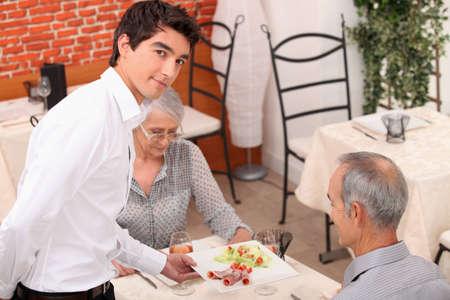 Joven camarero que sirve en el restaurante pareja de ancianos