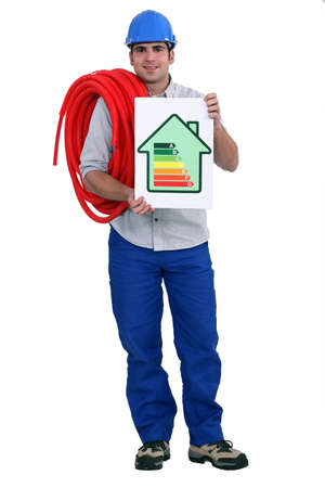 energy ranking: Man holding length of pipe and energy rating poster Stock Photo
