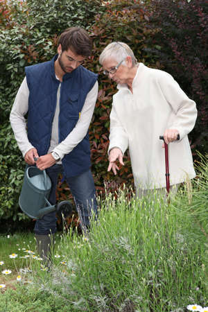 young man watering plants with older woman photo