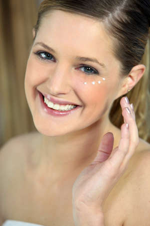 Woman applying under eye cream photo