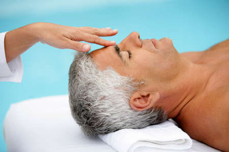 Mature man having facial massage photo