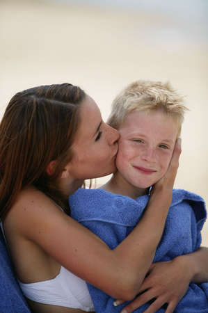 Woman kissing her son on a beach photo