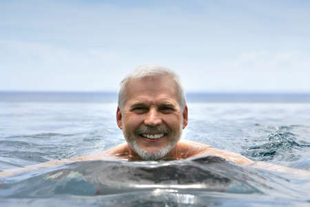 Elderly man swimming photo