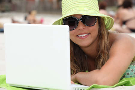 woman at beach using laptop photo