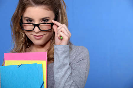 peer to peer: Young woman peering over her glasses Stock Photo