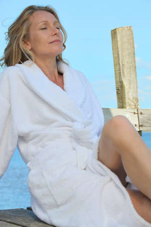40 45: Woman relaxing in the sunshine in a towelling robe