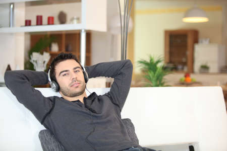 lying on couch: Man relaxing with music on sofa