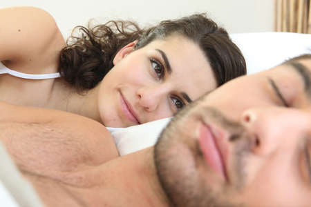 snooze: Woman looking at her husband sleeping