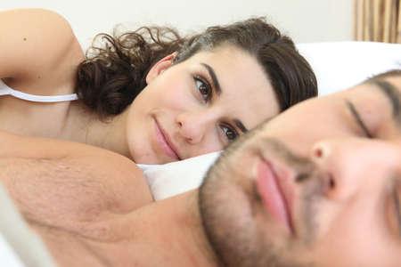 snoozing: Woman looking at her husband sleeping