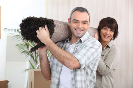 look pleased: Couple carrying rug