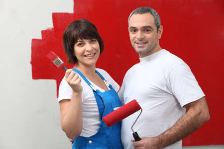 redecorating: Couple painting a room red