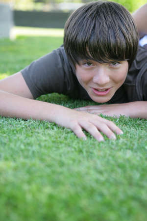 preteen boy: Preteen playing on the grass Stock Photo