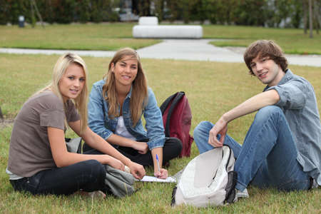 revising: Three students sat in the park working