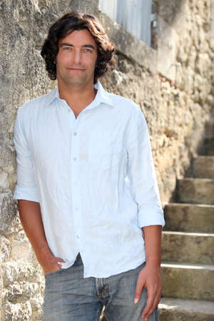 dark haired: Dark haired man leaning against old stone wall Stock Photo