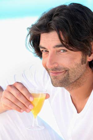 dark haired: Dark haired man drinking orange juice Stock Photo