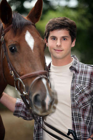 breeding: young man taking care of his horse Stock Photo