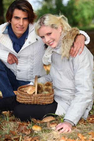 Couple gathering mushrooms in basket photo