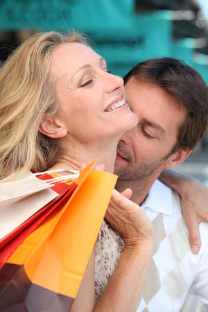 Man tenderly kissing her wife in the neck photo