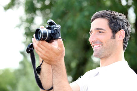takes: Happy relaxed man looking at the screen of his DSLR camera as he takes a photograph Stock Photo