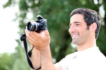 amateur: Hombre relajado feliz mirando la pantalla de su cámara DSLR como él toma una fotografía