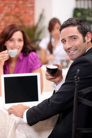 Couple drinking expresso in a cafe with a laptop screen left blank for your image photo