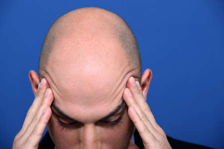 hand on forehead: Bald executive under pressure Stock Photo