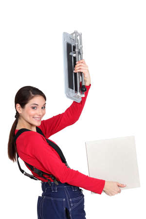 Tradeswoman holding up a tile cutting machine and a tile photo