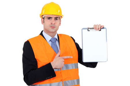 Engineer pointing to a clipboard photo