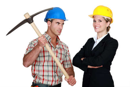 Builder aiming his pickaxe at a smiling architect photo