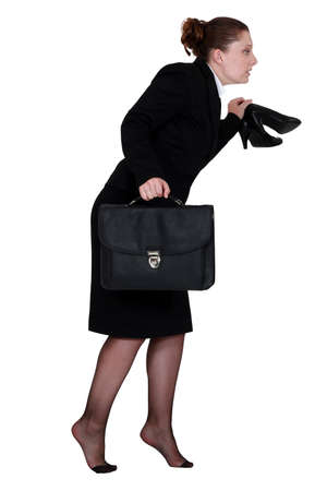 furtively: Woman sneaking out of the office Stock Photo