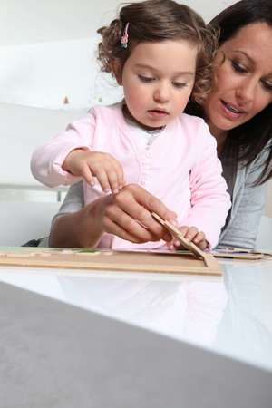 nanny: Little girl and nanny making a puzzle Stock Photo