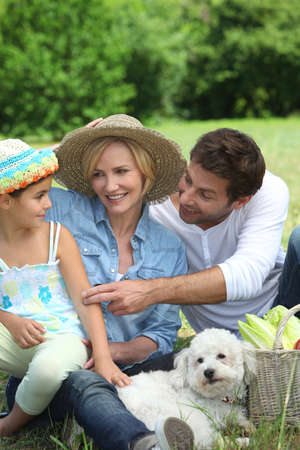 Family with small white dog photo